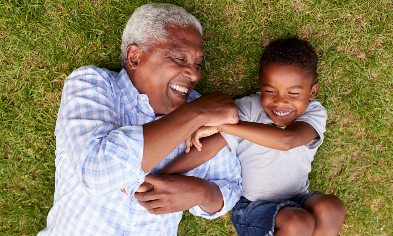 Grandfather and grandson tickle each other and laugh as they lay on the green grass
