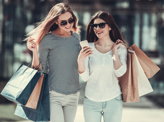 Two women shopping and looking at mobile phone