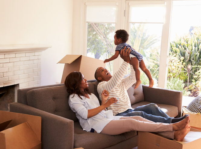 Family of three sitting on their couch in new home with moving boxes around them