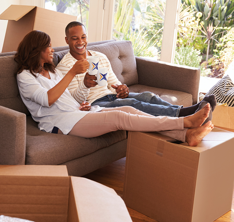 Couple sitting on couch with feet propped up on  boxes enjoying a cup of coffee in their new home.
