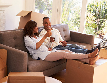 Couple drinking coffee in new home while sitting on couch.