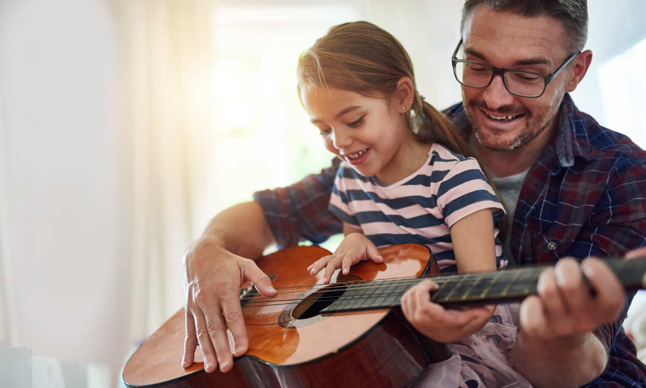 A father and daughter play the guitar happily