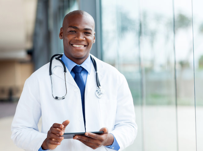 Physician smiles as he hold a tablet in his hands