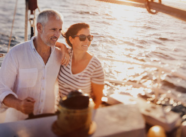Mature couple look onward while they boat