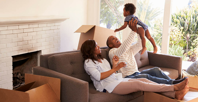 Family sitting on couch celebrating new home holding baby boy up in the air