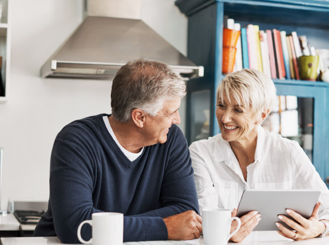 Man and woman sit happily at the kitchen island in discussion while holding a tablet