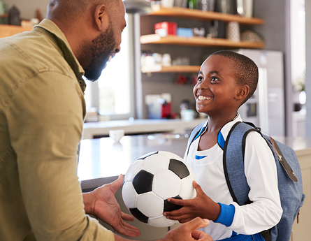 African American Dad and son looking at each other holding a soccer ball.