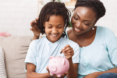 Mother helping daughter save money in piggy bank