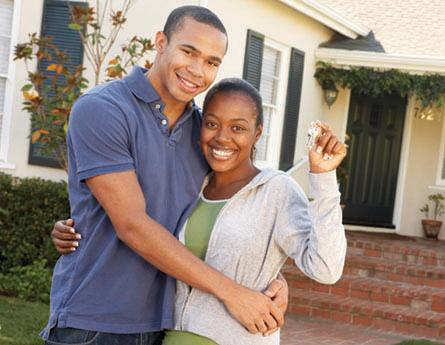 Couple in front of newly purchased home.