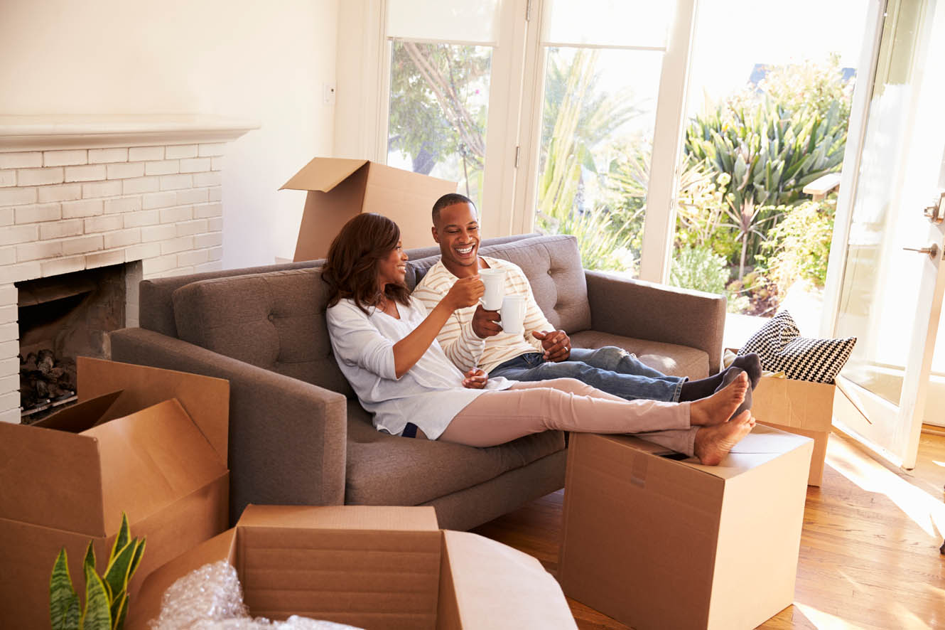 Couple moving into new home drinking coffee on the couch